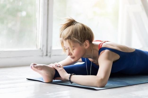 Giovane donna che fa yoga o esercizio e posa dei pilates.