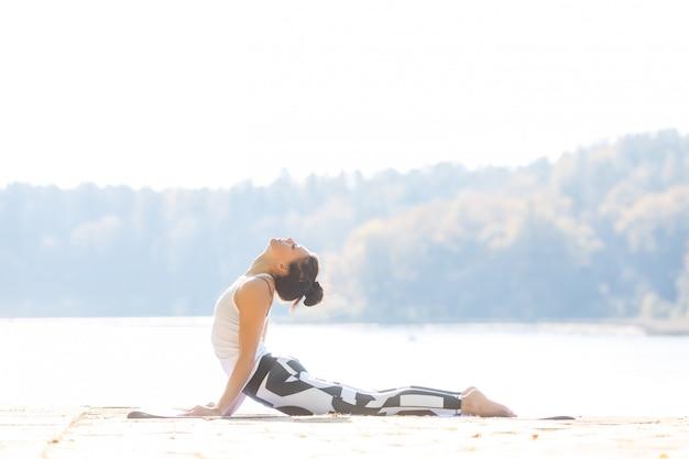 Giovane donna che fa yoga vicino al lago all'aperto, meditazione. sport fitness ed esercizio fisico in natura. tramonto d'autunno.