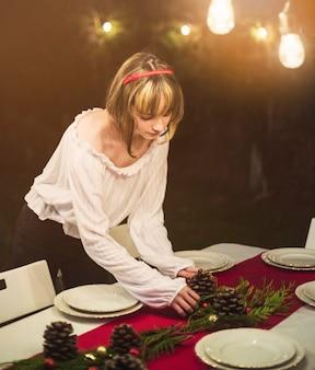 Giovane donna che fissa la tavola per la cena di natale