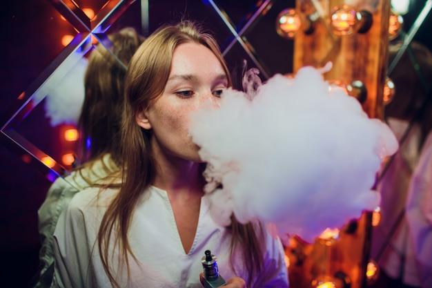 Giovane donna che fuma sigaretta elettronica contro lo sfondo degli specchi