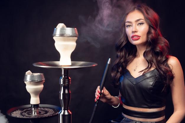 Giovane donna che fuma un narghilé