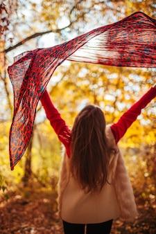Giovane donna che funziona con una sciarpa nella foresta