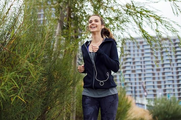Giovane donna che funziona nell'ambiente urbano