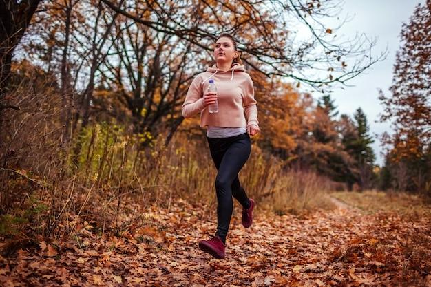 Giovane donna che funziona nella foresta di autunno.