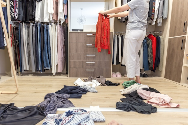 Giovane donna che getta vestiti in cabina armadio, disordine nel guardaroba e spogliatoio
