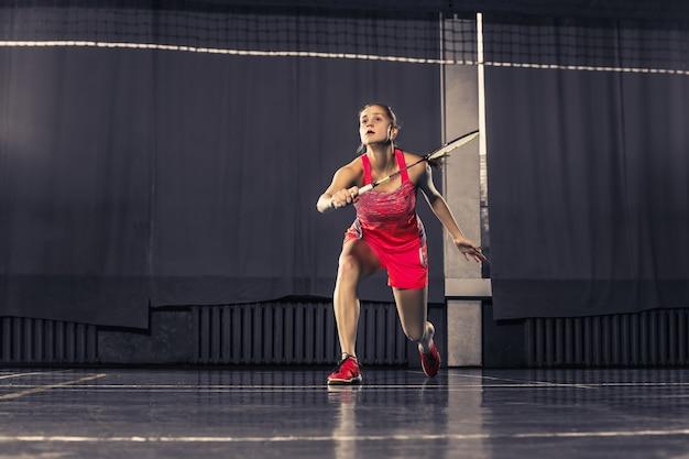 Giovane donna che gioca a badminton in palestra