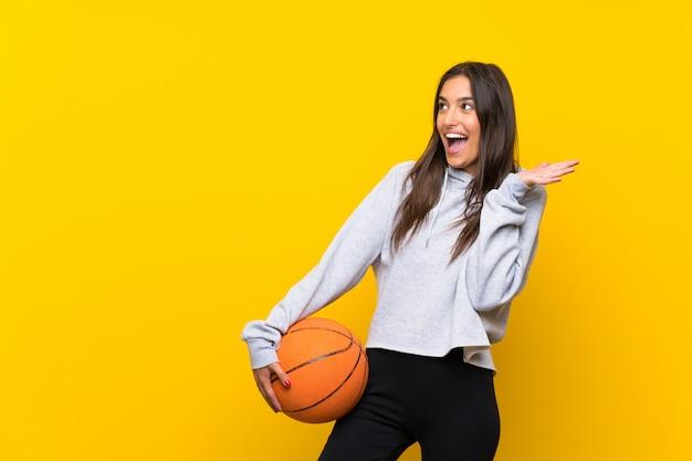 Giovane donna che gioca a basket isolato su giallo con espressione facciale a sorpresa