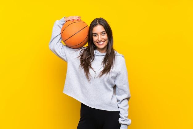 Giovane donna che gioca a basket sopra la parete gialla isolata