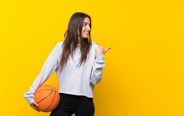 Giovane donna che gioca a basket sul muro giallo isolato che punta verso il lato per presentare un prodotto