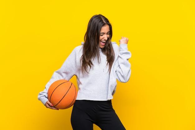 Giovane donna che gioca a pallacanestro sopra la parete gialla isolata che celebra una vittoria