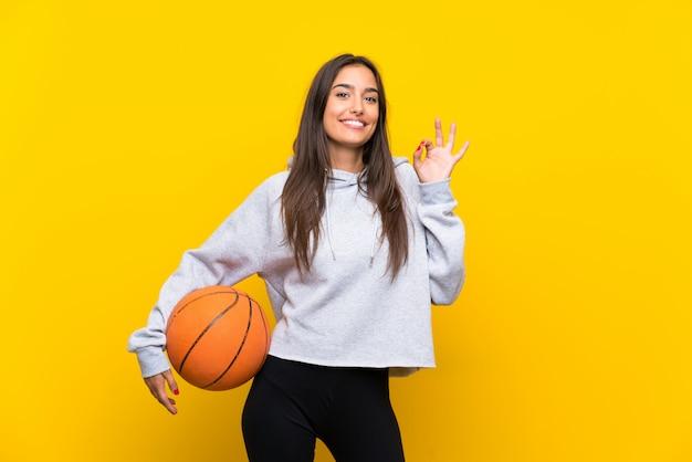 Giovane donna che gioca a pallacanestro sopra la parete gialla isolata che mostra segno giusto con le dita