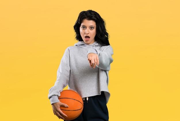 Giovane donna che gioca a pallacanestro sorpresa e che indica parte anteriore