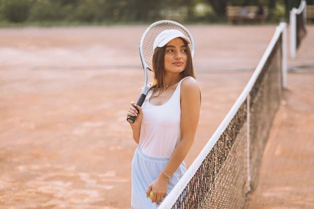 Giovane donna che gioca a tennis alla corte