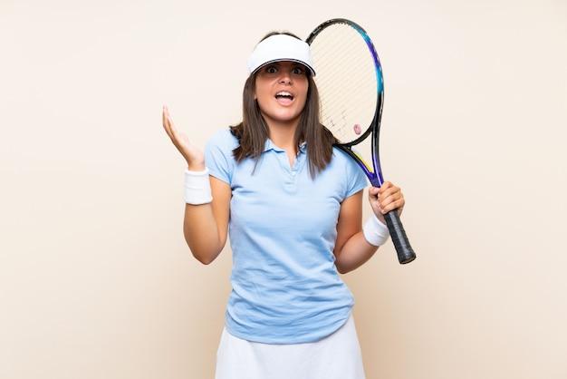 Giovane donna che gioca a tennis sopra la parete isolata con espressione facciale colpita