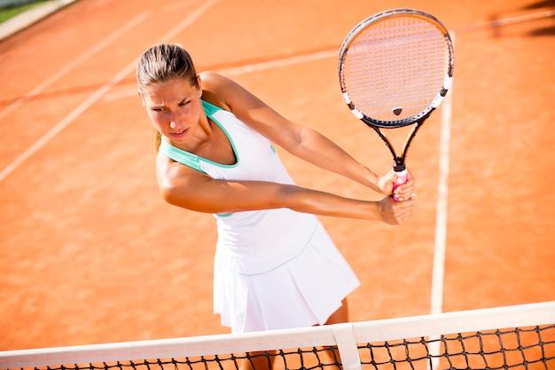 Giovane donna che gioca a tennis sull'argilla