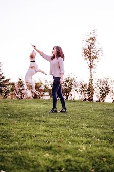 Giovane donna che gioca con il suo cane al parco. cane che salta
