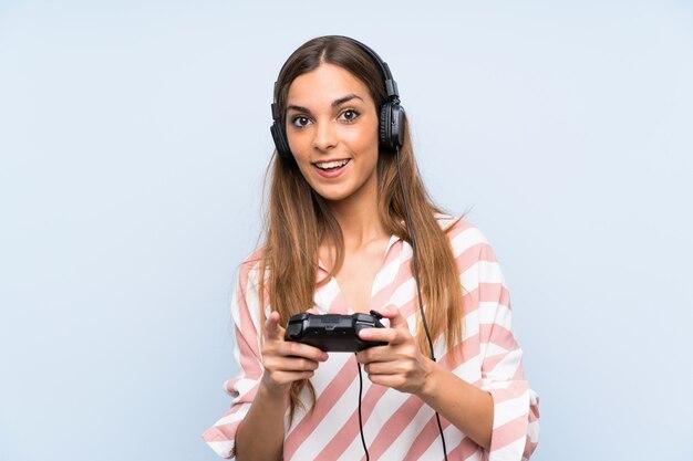 Giovane donna che gioca con un controller di videogioco sul muro blu
