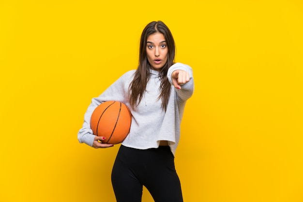 Giovane donna che gioca pallacanestro isolata sul giallo sorpreso e che indica parte anteriore