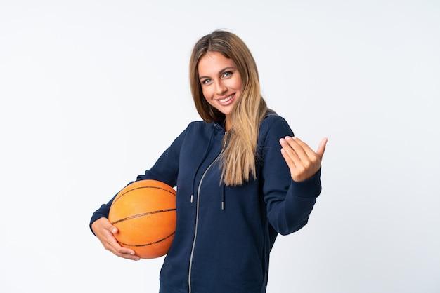 Giovane donna che gioca pallacanestro sopra bianco isolato