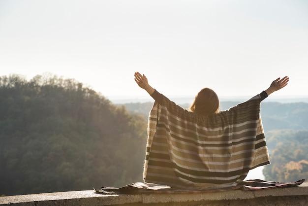 Giovane donna che gode del giorno soleggiato che si siede su una collina. mani alzate. vista posteriore