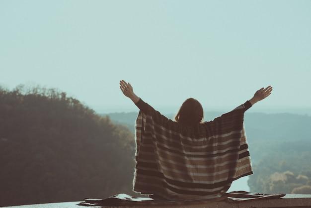 Giovane donna che gode del giorno soleggiato su una collina. mani alzate. vista posteriore