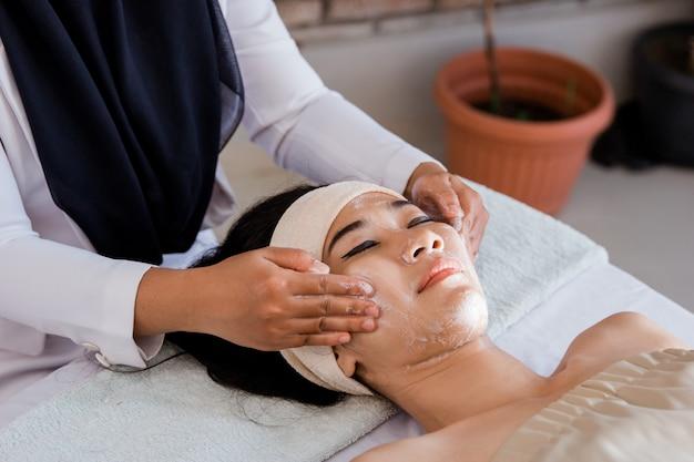 Giovane donna che gode del massaggio con la crema della maschera