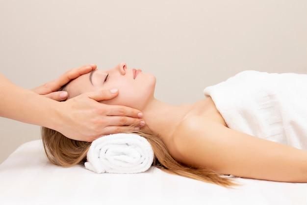 Giovane donna che gode del massaggio nel salone della stazione termale. massaggio viso. primo piano della giovane donna che ottiene trattamento di massaggio della stazione termale al salone della stazione termale di bellezza. cura della pelle e del corpo della stazione termale. trattamento di bellezza per il viso. cosmetologia.