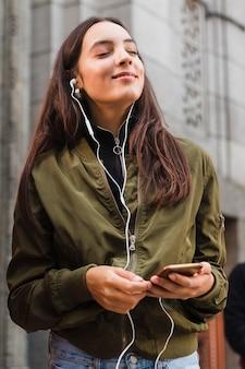 Giovane donna che gode della musica sul trasduttore auricolare per mezzo del telefono mobile