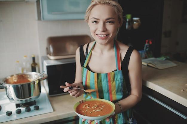 Giovane donna che gode della zuppa di zucca