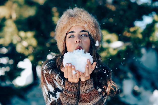 Giovane donna che gode delle montagne nevose in inverno