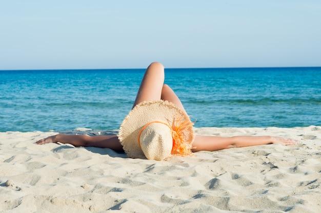 Giovane donna che gode di prendere il sole sulla spiaggia bianca