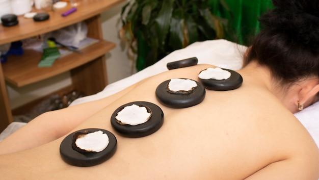 Giovane donna che gode di un massaggio con le rocce calde in un salone della stazione termale
