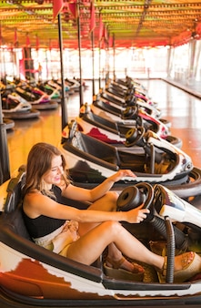 Giovane donna che gode guidando l'automobile di paraurti al parco di divertimenti