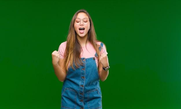 Giovane donna che grida aggressivamente con un'espressione arrabbiata o con i pugni chiusi celebrando successo sul verde