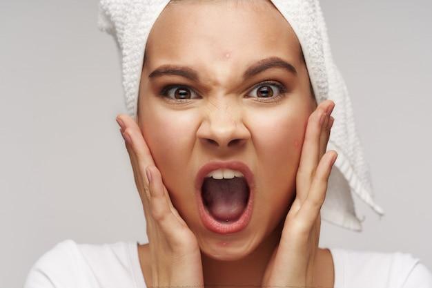 Giovane donna che grida all'avviso di un brufolo sulla sua fronte