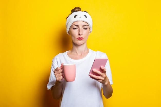Giovane donna che guarda il telefono in una benda per dormire e con una tazza di caffè su uno sfondo giallo.