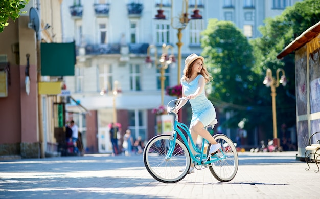 Giovane donna che guarda intorno mentre ciclando nel centro urbano