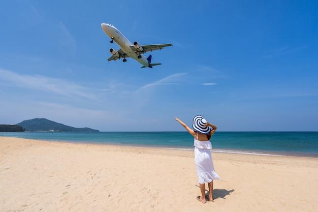 Giovane donna che guarda un aeroplano
