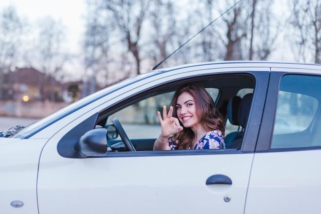 Giovane donna che guida un'auto in città. ritratto di una bella donna in macchina, guardando fuori dalla finestra e sorridente. concetti di viaggio e vacanze
