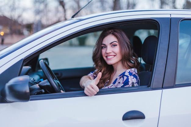 Giovane donna che guida un'auto in città.
