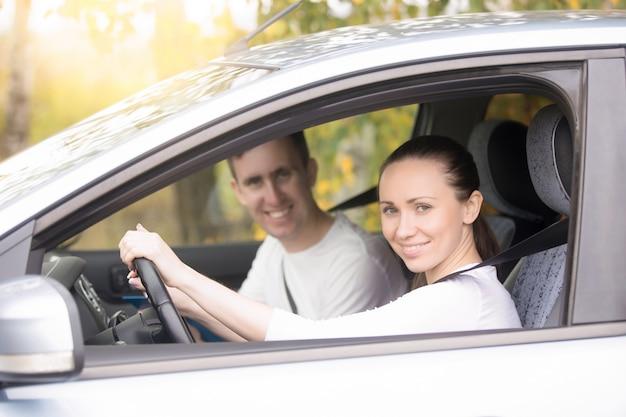 Giovane donna che guida, un uomo seduto vicino in macchina