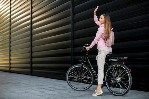Giovane donna che guida una bicicletta elettrica nell'ambiente urbano