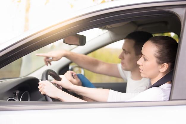 Giovane donna che guida, uomo che punta la direzione