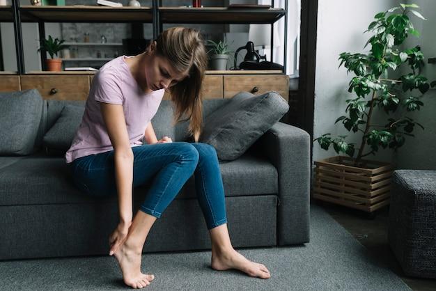 Giovane donna che ha dolore al piede tallone
