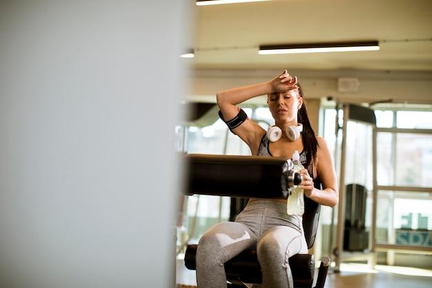 Giovane donna che ha esercizi sull'estensione della gamba e la macchina dell'arricciatura della gamba in palestra