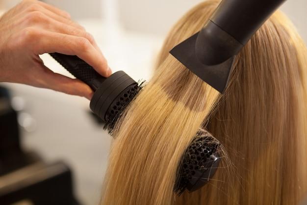 Giovane donna che ha i capelli disegnati dal parrucchiere
