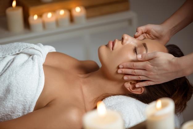 Giovane donna che ha massaggio viso rilassante nel salone spa.