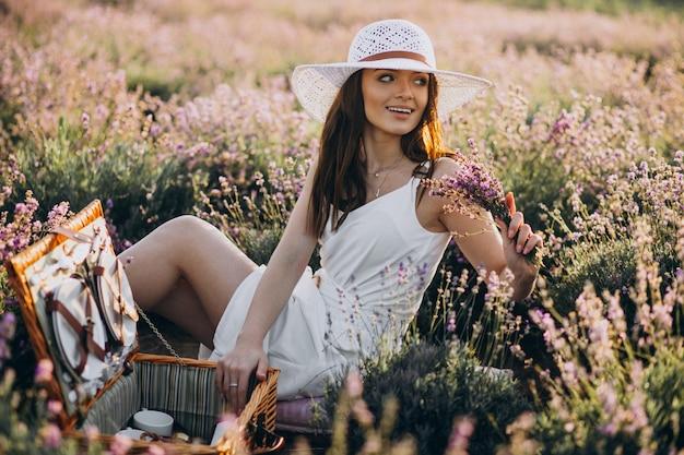 Giovane donna che ha picnic in un campo di lavanda