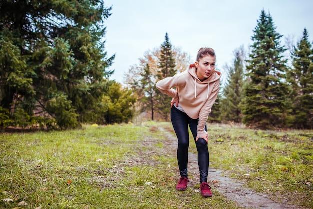 Giovane donna che ha resto dopo una corsa nella foresta di autunno