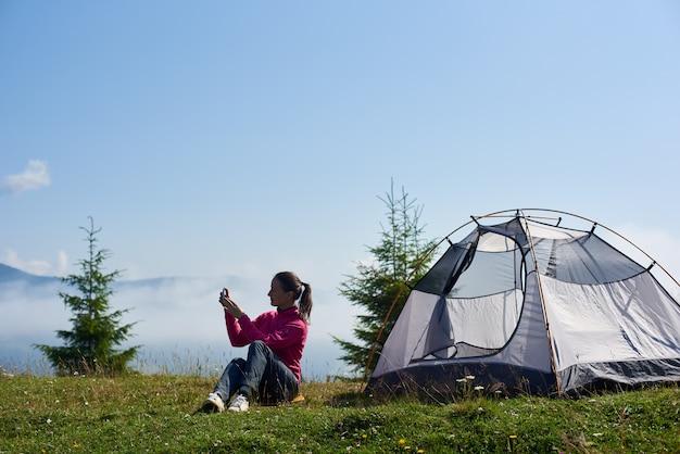 Giovane donna che ha un periodo di riposo vicino alla tenda turistica nella mattina d'estate in montagna